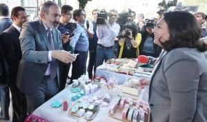 Nigol Pashinian conversa con una comerciante mientras visita una feria de arte y artesanía sirio-armenia en Ereván
